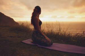 Side view shot of fitness woman sitting in Vajrasana pose on exercise mat and looking at sunset. Female practicing yoga on the cliff during sunset.
